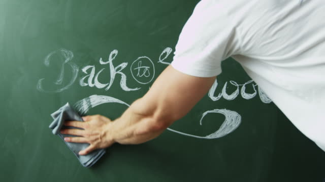 Back to school, man cleaning text from chalkboard, close up, shot on R3D video