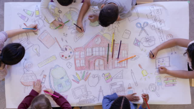 Back to School Overhead aerial view of small group of elementary age children colouring and drawing a back to school scene on white paper using pencil crayons. recreational pursuit stock videos & royalty-free footage