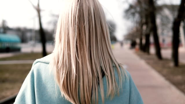 Back view blonde woman walking and looking left. Caucasian girl in blue coat with beautiful long fair hair. Slow motion