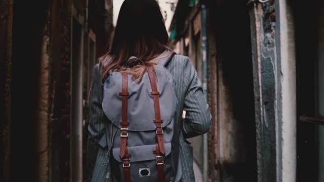 vídeos de stock e filmes b-roll de back view businesswoman with backpack wearing fashionable suit walking along dark street in venice, italy slow motion. - mochila saco