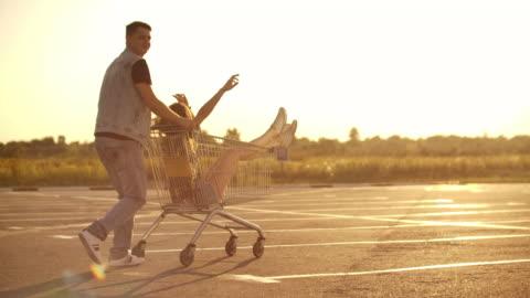 vista posteriore. allegra giovane coppia innamorata uomo e donna che ride e si diverte mentre guida i carrelli nel parcheggio del supermercato al rallentatore al tramonto - concetti e temi video stock e b–roll