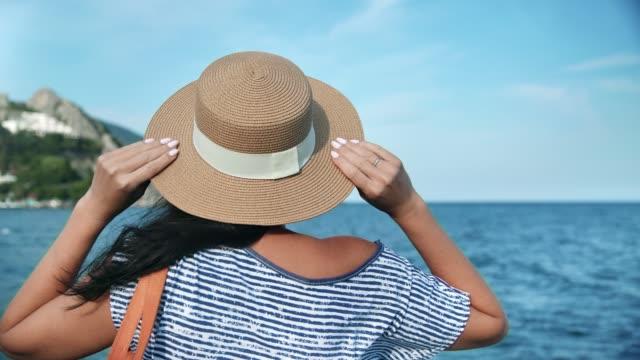 rückansicht elegante reisefrau in strohhut bewundern seelandschaft. mittlere aufnahme auf red-kamera - strohhut stock-videos und b-roll-filmmaterial