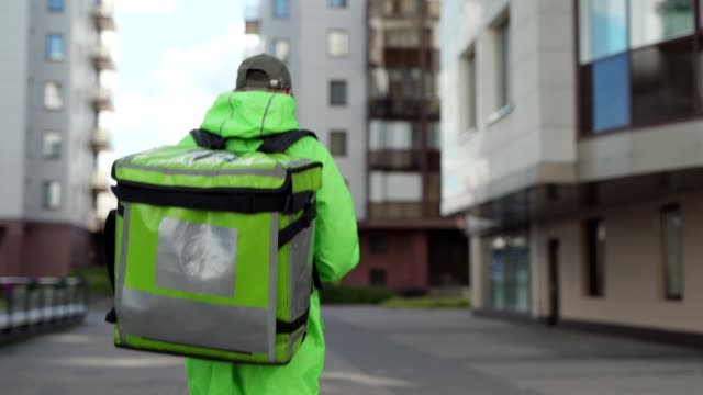 Video Back view follow shot of young male food courier in green uniform using mobile app on smartphone while walking down street with insulated backpack delivering food. Man coming to building door