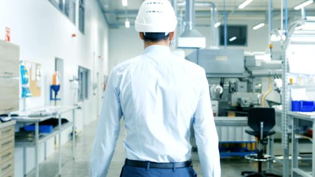 ラップトップを押しながらライトの近代的な工場を歩くハード帽子でチーフ エンジニアの背面の映像。現代の産業環境で成功すると、ハンサムな男。 - 後ろ姿点の映像素材/bロール
