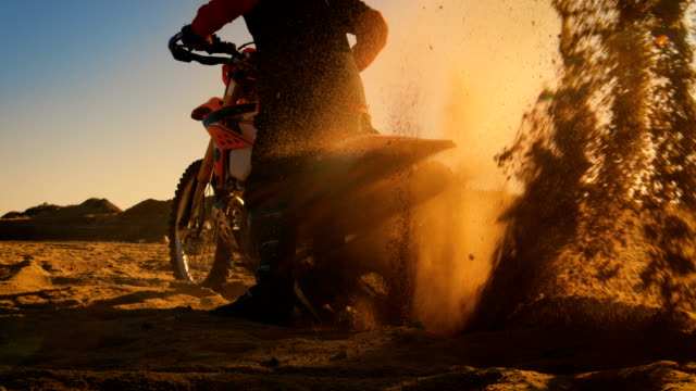 Back View Footage of the Professional Rider on the FMX Dirt Bike Twisting Full Throttle Handle and Digging into the Sand with His Back Wheel. video