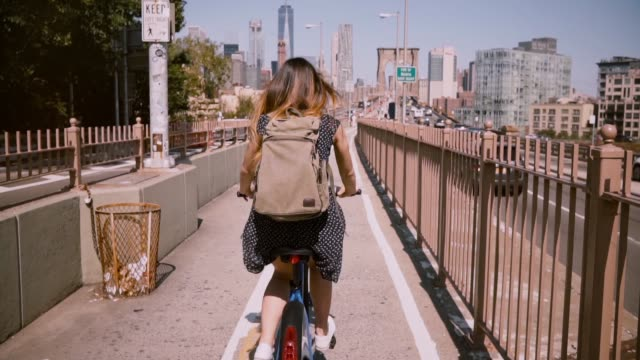 Back view happy woman with backpack riding a bicycle along a separate bike lane level on Brooklyn Bridge, New York City