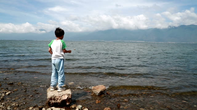Back view little boy standing and throwing a stones to the river