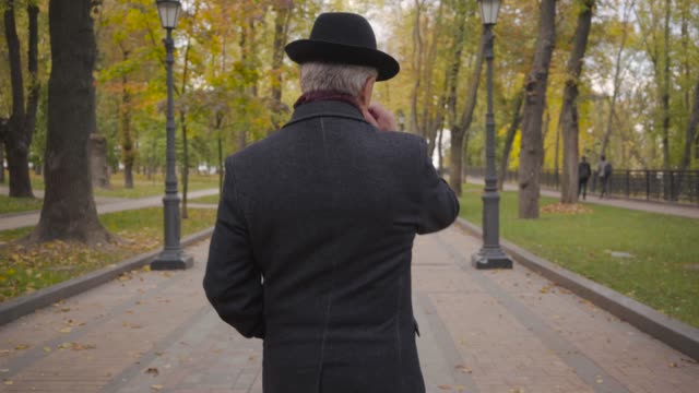 Back view of a Caucasian man with grey hair dressed in elegant black hat and coat strolling along the alley