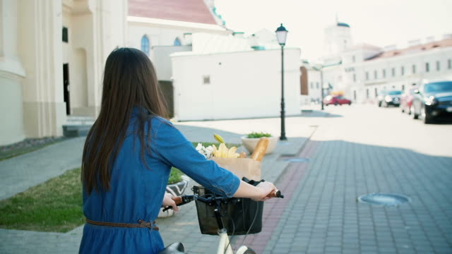 back view of a girl with waving hair walking her bike with flowers and bread in a basket, slow mo, steadicam shot - cestino della bicicletta video stock e b–roll