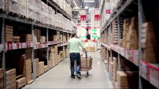 Une vue arrière d'un homme poussant un chariot plein de boîtes à ce sujet entre les étagères dans un entrepôt de stockage - Vidéo