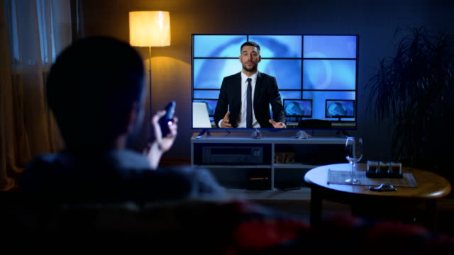 Zurück Ansicht eines Mannes, der auf einer Couch Watching Breaking News auf seinem großen Bildschirm TV sitzt. Es ist Abend. – Video
