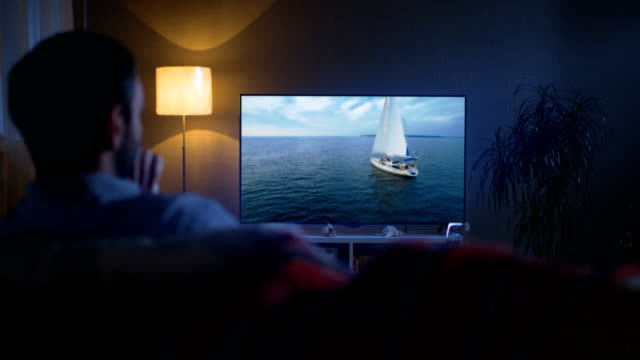 Back View of a Man Sitting on a Couch Watching Romantic Movie with Yachting and Camping in it on His Big Screen TV. It's Evening. Back View of a Man Sitting on a Couch Watching Romantic Movie with Yachting and Camping in it on His Big Screen TV. It's Evening. Shot on RED EPIC-W 8K Helium Cinema Camera. watching tv stock videos & royalty-free footage
