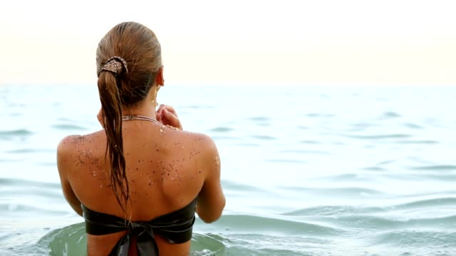 Back view of a sexy woman with ponytail standing in the water She turns around and looks in the camera. Slowmotion shot