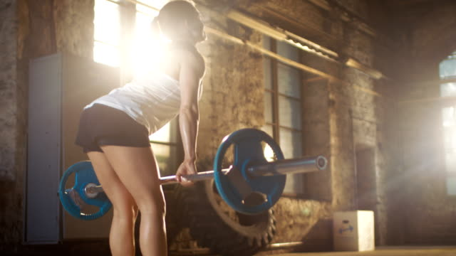 Back View of a Strong Athletic Woman Lifting Barbell as Part of Her Cross Fitness Bodybuilding Gym Exercise. video