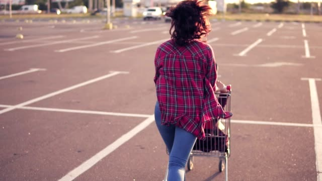 Back view of a young woman sitting in the grocery cart, while her friend is pushing her behind in the parking by the shopping mall, enjoying outdoors with shopping trolley race during sunset Back view of a young woman sitting in the grocery cart, while her friend is pushing her behind in the parking by the shopping mall, enjoying outdoors with shopping trolley race during sunset. woman pushing cart stock videos & royalty-free footage