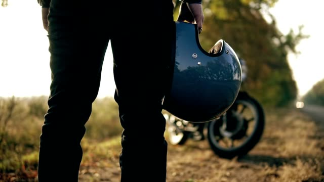 Back view of an unrecognizable man in black jeans and leather jacket holding his helmet in his hand while standing by his cool bike on a sunny day in autumn in forest video