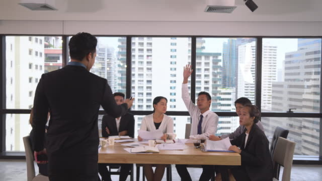 vídeos de stock e filmes b-roll de back view of asian businessman coaching and presenting to businesspeople in modern workplace. employees raise hand to ask question - training