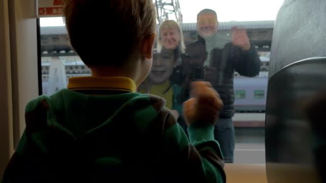 鉄道および別れの] ウィンドウで腕を振る彼の祖父母を見て少年の背面図 ビデオ