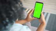 istock Back view of brunette holding chroma key green screen smartphone watching content 1201655256