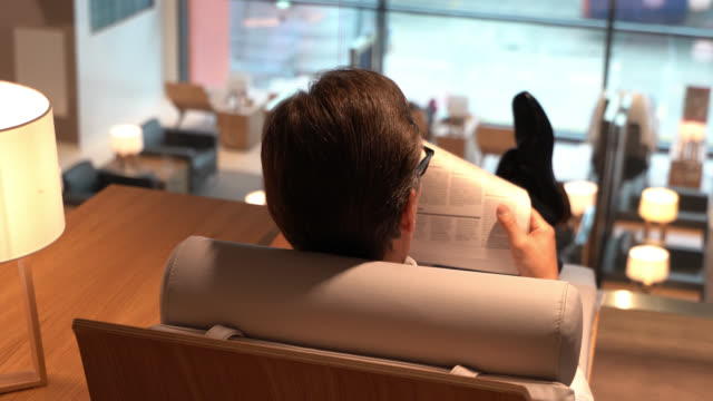 stockvideo's en b-roll-footage met achteraanzicht van zakelijke man ontspannen in de vip-lounge van de luchthaven een nieuws document lezen - vliegveld vertrekhal