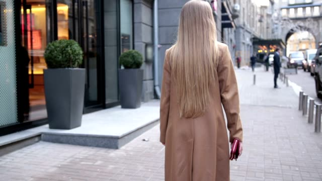 Back view of business woman walking on city street video