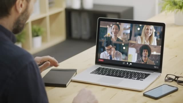 Back view of businessman joining a remote call with multi ethnic colleagues from home. Business Remote meeting or remote conference. Multi ethnic team video call.