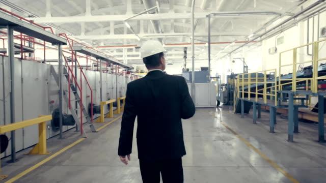 rückansicht des kaufmanns zu fuß durch fabrik - rücken stock-videos und b-roll-filmmaterial