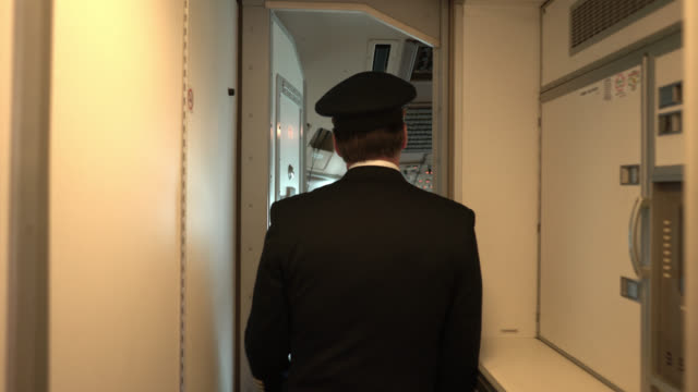 back view of captain walking into the cockpit - pilota video stock e b–roll