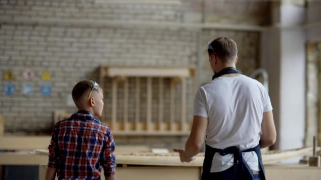 Back view of carpenter and his little son walking towards workbench in carpentry shop. Father showing and explaining cheerful kid how to construct wooden boat model