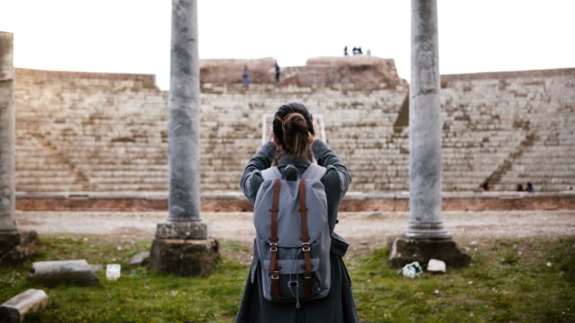 back view of caucasian tourist girl with backpack taking smartphone photo of ancient amphitheater pillars in ostia italy - cartina italia video stock e b–roll