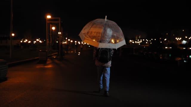 Back view of child walking under umbrella in dark in the rain, slow motion. video