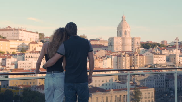 vídeos de stock e filmes b-roll de back view, of couple embracing while standing on embankmentand looking at the city of lisbon in morning sun light - people lisbon