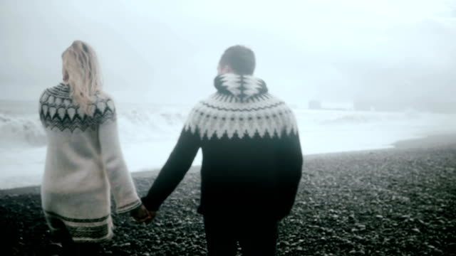 Back view of couple holding hands and walking on the shore of black beach in Iceland. Tourists exploring famous sight.