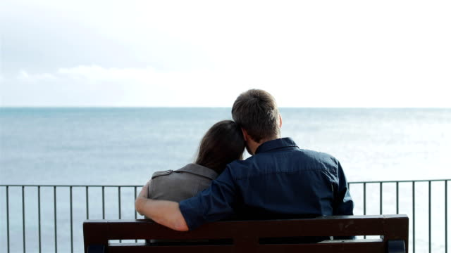 Back view of couple looking at ocean Back view of a couple in love hugging looking at ocean sitting on a bench on the beach heterosexual couple stock videos & royalty-free footage