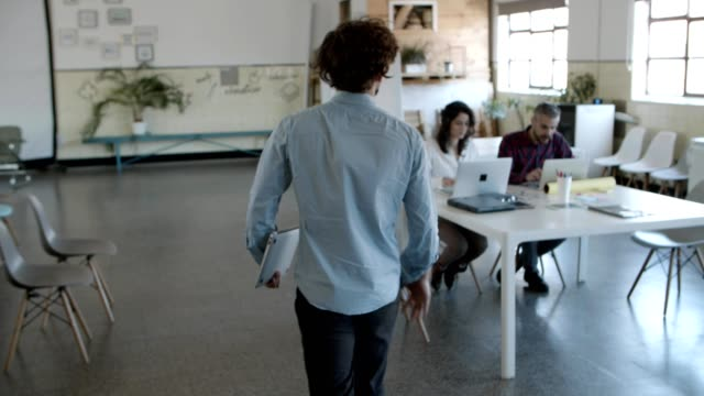 Back view of curly man walking to cheerful colleagues