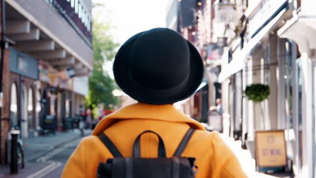 stockvideo's en b-roll-footage met achteraanzicht van modieuze jonge zwarte vrouw het dragen van een hoed en een gele erwt jas lopen in de straat en draaien om terug te kijken naar de camera - street style
