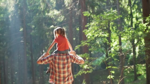 Back view of father giving a piggyback ride to daughter walking in forest.Father holding daughter on shoulders hiking along forest trail path.Father and daughter hiking on forest path together