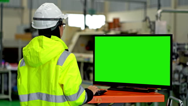 4K Back View Of Female Industrial Engineer Using A Computer With Green Screen Monitor Working In A Heavy Industry Manufacturing Factory 4K Female Industrial Engineer Using A Computer With Green Screen Monitor For Your Message manufacturing equipment stock videos & royalty-free footage