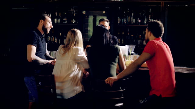 back view of four young friends relaxing at bar counter talking with barman on the other side of wooden table. company of people in casual clothes are having break together speaking with bartender - bartender stock videos and b-roll footage
