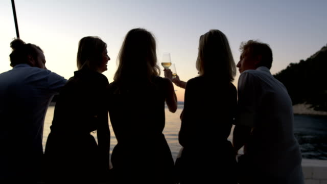 vídeos y material grabado en eventos de stock de vista posterior de grupo de cinco jóvenes tintineos de copas de champagne en un yate y admirando el atardecer marino. - yacht