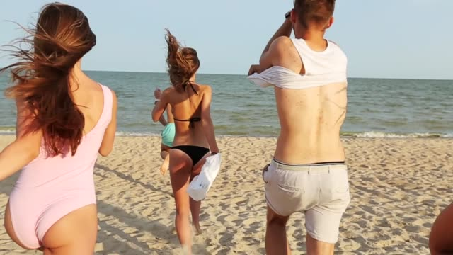 back view of group of friends undress running into the sea water on sunset and throw shirts on the beach. cheerful happy people having fun on the beach. men and women go to swim in slow motion - koszula filmów i materiałów b-roll