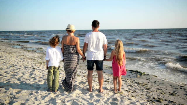 Back View of Happy Family Looking on the Sea During Summer Vacation. Mother, Father, Son and Daughter Holding Hands on the Beach video