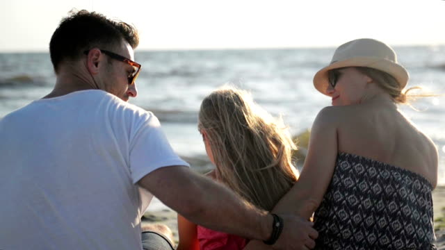 Back View of Happy Family Sitting on the Beach and Hugging Enjoying Warm Sunny Day During Summer Vacation video