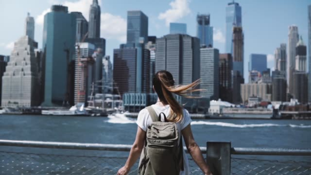 Back view of happy female tourist with backpack raising arms wide open at New York skyline view, looking back at camera video