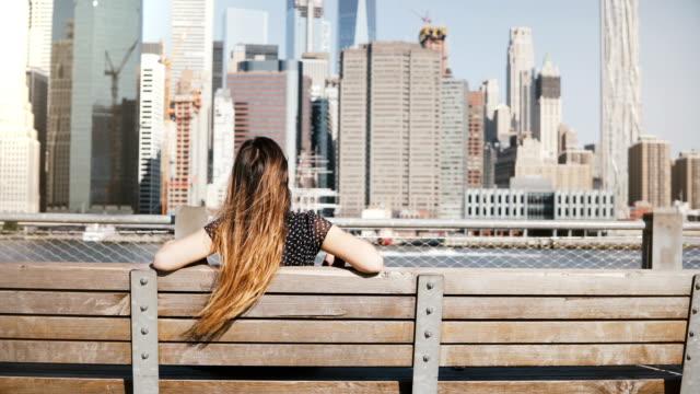 幸せな女の子の長い飛行髪楽しんで素晴らしいマンハッタン スカイライン ビュー ベンチに座って腕を大きく開いて背面します。 - ベンチ点の映像素材/bロール