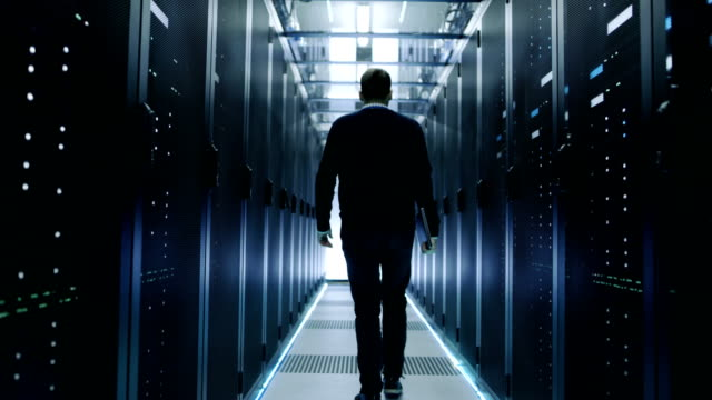 Back View of IT Engineer Walking Through Data Center with Working Rack Servers. video