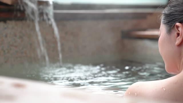 온천에 흠뻑 젖어 일본 여자의 뒷면 - 스파 온천 스톡 비디오 및 b-롤 화면