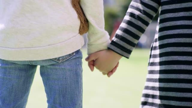 公園で手をつないでいる日本人姉妹のバックビュー - 兄弟姉妹点の映像素材/bロール