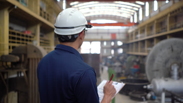 Back view of latin american supervisor overseeing operations at a metallurgic factory video