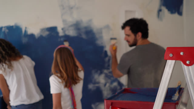Back view of latin american young family painting a wall with blue at home